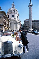 Bridal Couple near oldtimer at square, Chiesa del Santissimo, Rome, Lazio, Italy