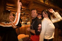Two girls and a man dancing and enjoying an Apres_ski party at Purzelbaum Alm, Flachau, Salzburger Land, Austria