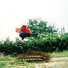 Boy jumping above rusty wire