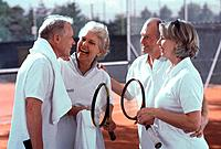 Two senior couples talking on tennis court