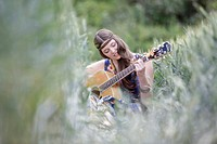 Young woman with guitar in corn field