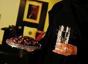 Arab lady with henna on hands holding dates and water