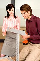 Man setting up office table, woman assisting