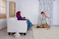 Woman holding the television remote control, daughter playing around