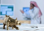 Bull figurine on newspaper, background computers and Arab up_up