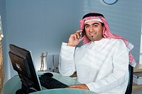 Arab man with cellphone at the office, smiling