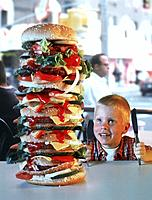 Young boy looking at very tall hamburger in fast food restaurant