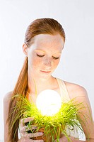 woman with energy saving light bulb in plant