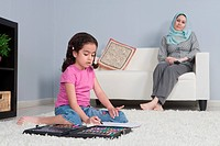 Arab mother with daughter doing homework in the living room