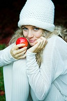 Young woman eating apple in park