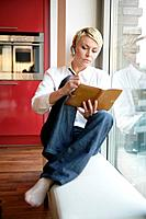 Woman with Hands-Free Device and Diary Sitting Beside Window