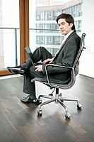 Business Man Sitting with Laptop on Office Chair in Empty Room