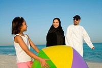Girl holding beach ball while parent looking at her
