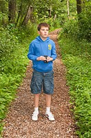 An eleven year old boy birdwatching with binoculars at Fairhaven woodland and water garden in South Walsham , Norfolk , England , Britain , Uk