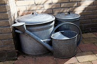 Still life of watering can and to vats in the garden. The Netherlands