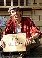 Homeless Man Sitting on Sidewalk