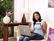 Lady using laptop holding white card printed vote in English MR702U