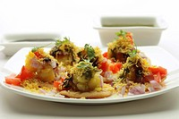 Fast food , chat chaat sev puri toppings of chutney tomato onion and sev in plate on white background