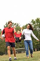 Man and Woman Swinging Excited Girl on Soccer Field