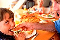Boy biting into a piece of pizza, cropped, blurred