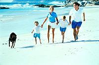 Family and dog running on beach, full shot