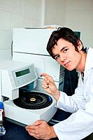 Portrait of a a student posing with a centrifuge while looking at the camera