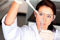 Brunette woman pouring a liquid in a tube in a laboratory