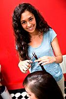 Portrait of a smiling female hairdresser cutting hair with scissors