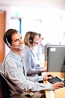 Portrait of a smiling customer assistant using a headset in a call center