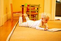 Little Boy Reading Book on Floor