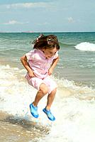 A LITTLE GIRL JUMPING OVER WAVES HAVING FUN DURING SUMMER AT THE
