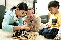 Parents Playing Chess with Young Son