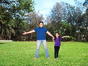 Man with her daughter on grass lawn , Mumbai , India , Asia MR779P , MR779S