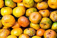 A stack of healthy ripe fresh mandarins for sale at a rural market.