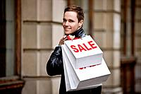A young man holding carrier bags (thumbnail)
