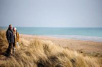 A senior couple walking amongst sand dunes, looking out to sea (thumbnail)