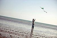 A senior woman flying a kite on the beach