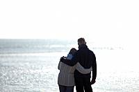A senior couple looking out to sea, embracing