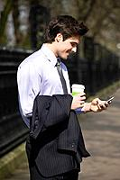A businessman holding a hot drink, looking at his mobile phone (thumbnail)