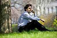 A businessman sitting on the grass, talking on the phone