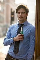 A businessman holding a bottle of beer