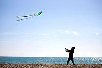 A young man flying a kite on the beach