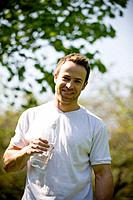 A young man holding a bottle of water, outdoors (thumbnail)