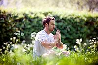 A young man meditating outdoors