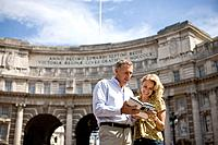 A middle_aged couple standing in front of Admiralty Arch, looking at a guidebook