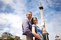 A middle_aged couple in front of Nelson's column, holding a guidebook