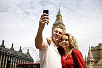 A middle_aged couple standing at Parliament Square, taking a photograph