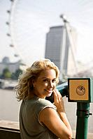 A middle_aged woman using a telescope in front of the London Eye