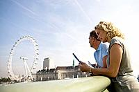 A middle_aged couple standing near the London Eye, looking at a guidebook