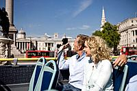 A middle_aged couple sitting on a sightseeing bus, taking photographs